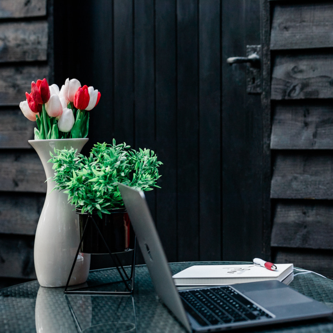 Laptop and flowers on outside table